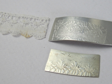 Lace pressed between silver and zinc makes an imprint.