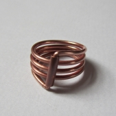 Bent into a ring, the two ends hidden in a copper tube.